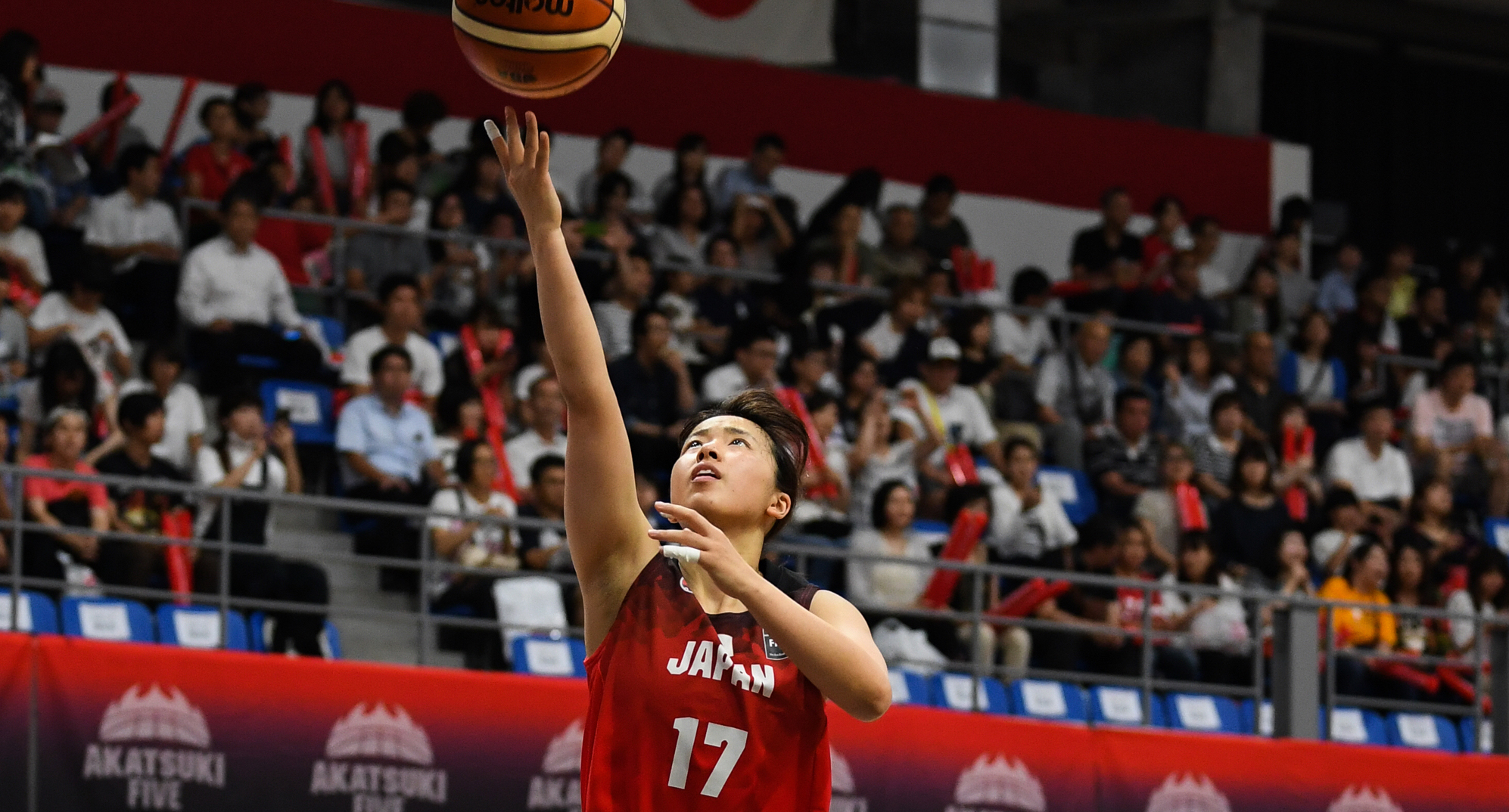 A basketball floats just above the tips of Naho's fingers as she lays it in for two points.